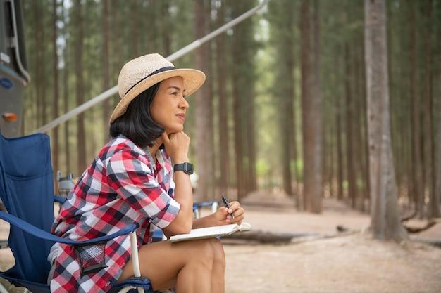 Kobieta patrząc na laptopa w pobliżu kempingu. wakacje z przyczepą kempingową. rodzinny wyjazd na wakacje, wyjazd wakacyjny w kamperze. kobieta czytająca książkę w bagażniku samochodu. kobieta ucząca się na przerwie w podróży, r