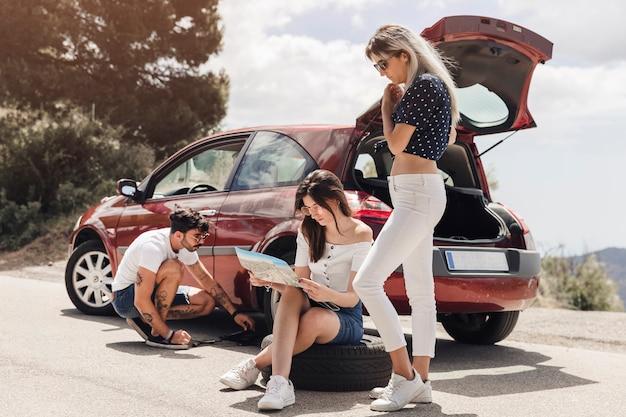 Kobieta patrząc na mapę w pobliżu człowieka, badając zepsuty samochód