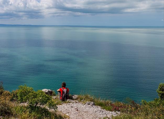 Kobieta patrząc na morze adriatyckie od krawędzi krasu w pobliżu triestu we włoszech