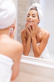 Kobieta patrząc na odbicie w lustrze po prysznicu