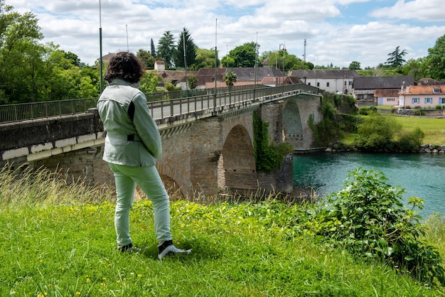 Kobieta patrząc na starożytny most na rzece gave d'oloron w mieście navarrenx we francji
