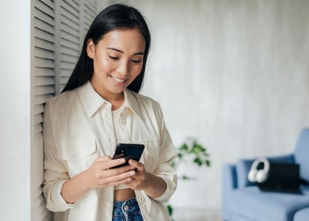 Kobieta patrząc na swój telefon z domu