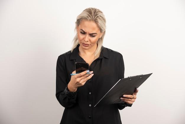 Kobieta, patrząc na telefon komórkowy i trzymając schowek ołówkiem. wysokiej jakości zdjęcie