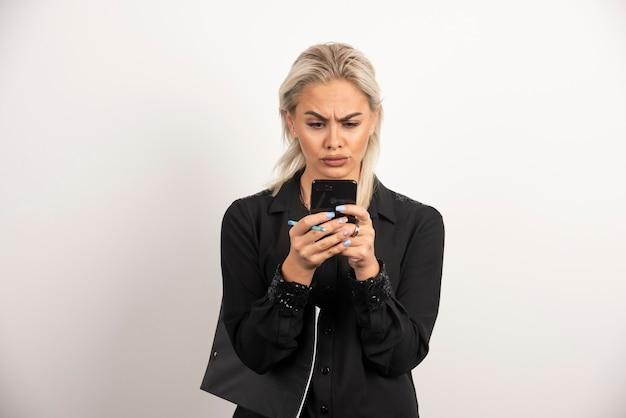 Kobieta, patrząc na telefon komórkowy i trzymając schowek. wysokiej jakości zdjęcie