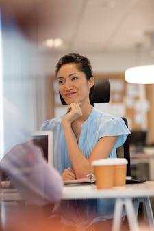 Kobieta patrząc od biurka w biurze
