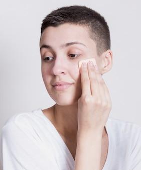 Kobieta, patrząc od hotelu podczas czyszczenia twarzy
