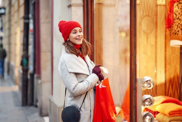 Kobieta patrząc przez okno sklepów