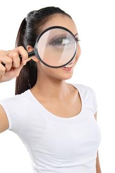 Kobieta patrząc przez szkło powiększające