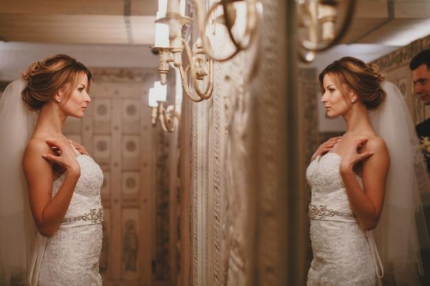 Kobieta patrząc swoją suknię ślubną w lustrze