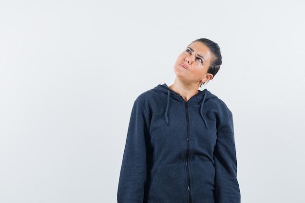 Kobieta patrząc w bluzę z kapturem i niezdecydowany, widok z przodu.