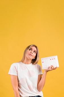 Kobieta patrząc w górę i trzymając kalendarz miesiączkowy