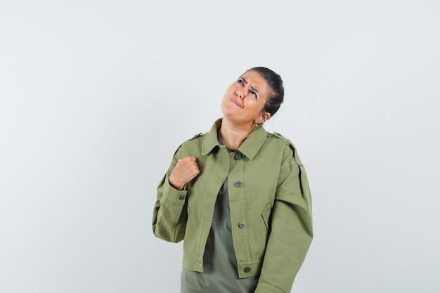 Kobieta patrząc w górę w kurtce, t-shirt i wyglądająca zamyślona