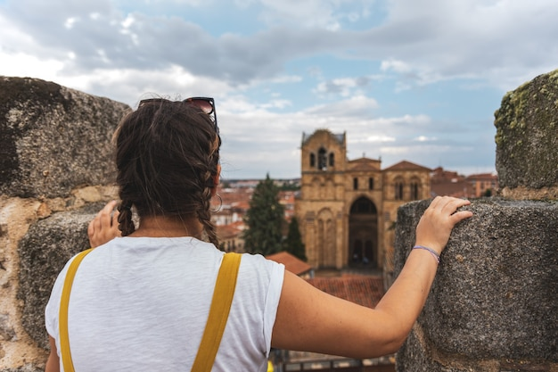 Kobieta patrząc w kierunku romańskiej świątyni bazyliki san vicente w avila, hiszpania. widok ze szczytu ściany.