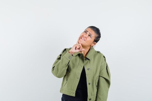Kobieta patrząc w kurtkę, t-shirt i niepewny patrząc.