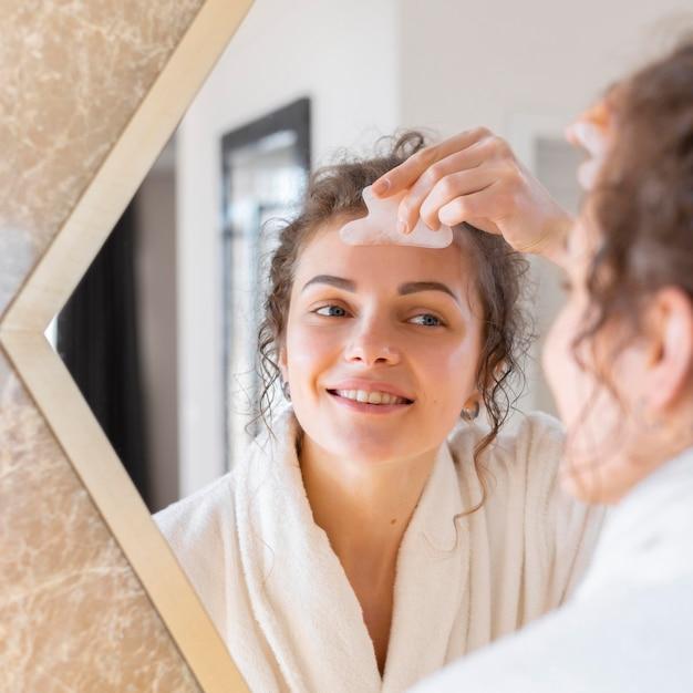 Kobieta, patrząc w lustro i robi masaż twarzy