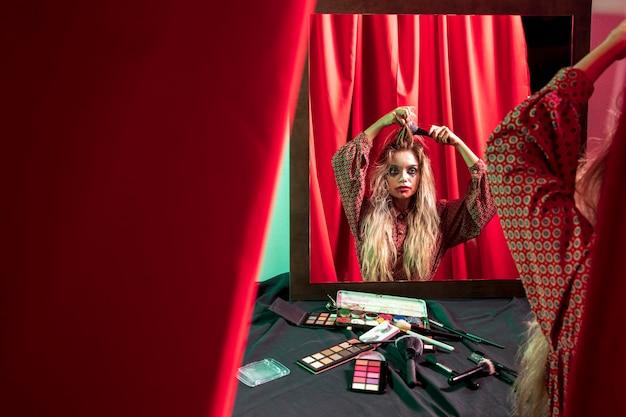 Kobieta, patrząc w lustro i szczotkowanie włosów
