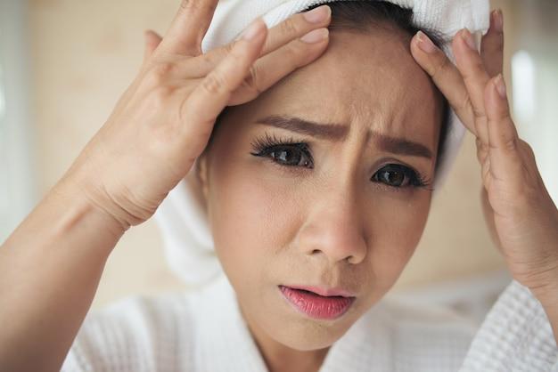 Kobieta patrząc w lustro w domu i sprawdzanie jej twarz