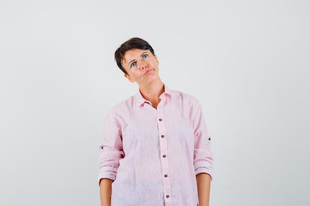 Kobieta patrząc w różową koszulę i wątpliwy, widok z przodu.