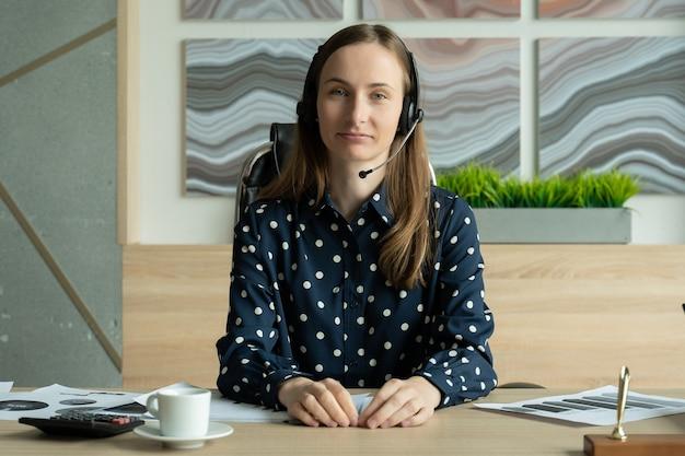 Kobieta patrząca i mówiąca przez kamerę internetową podczas wideokonferencji z biura