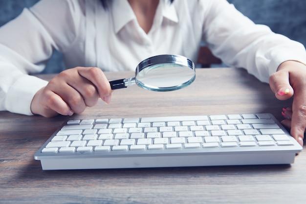 Kobieta patrząca na klawiaturę przez lupę