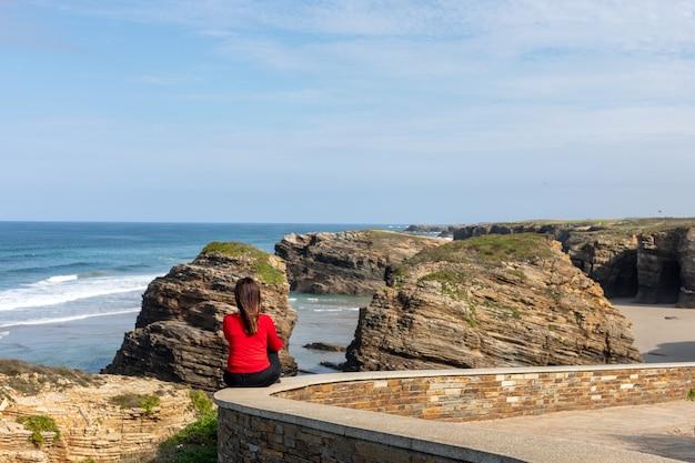 Kobieta patrząca na krajobraz plaży katedr w galicji hiszpania - playa de las catedrales