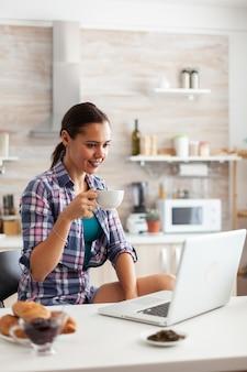 Kobieta patrząca na laptopa w kuchni trzymająca filiżankę z zieloną herbatą rano