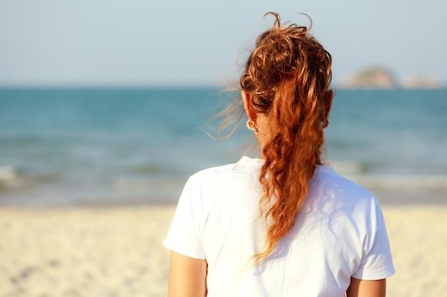 Kobieta patrząca na morze z tyłu