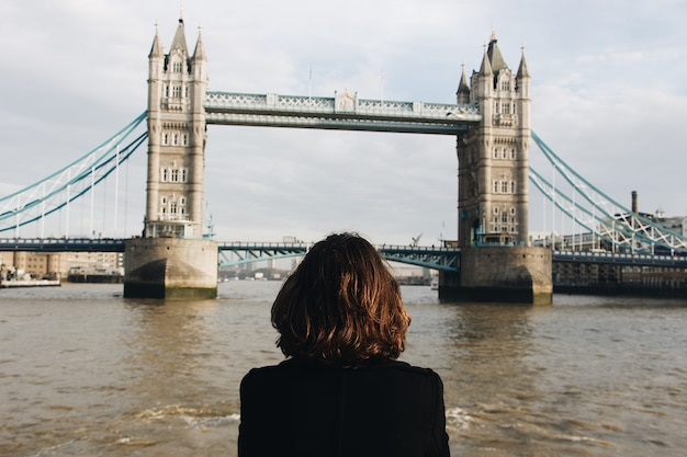 Kobieta patrząca na słynny tower bridge st uk podczas dziennego tower bridge w wielkiej brytanii