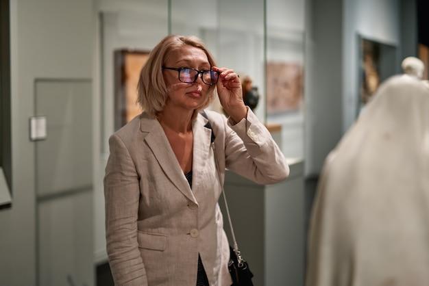 Kobieta patrząca na starą rzeźbę w galerii sztuki
