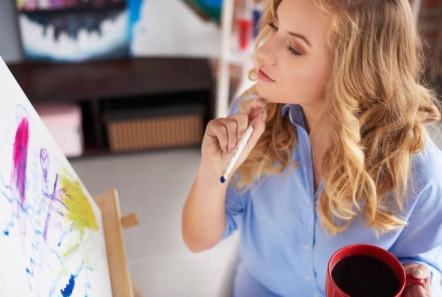 Kobieta patrząca na swój namalowany obraz