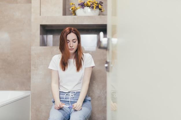 Kobieta patrząca na szybki pozytywny lub negatywny wynik testu ciążowego