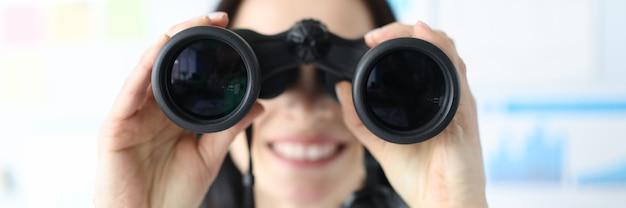 Kobieta patrząca w czarną profesjonalną lornetkę w biurowym zbliżeniu