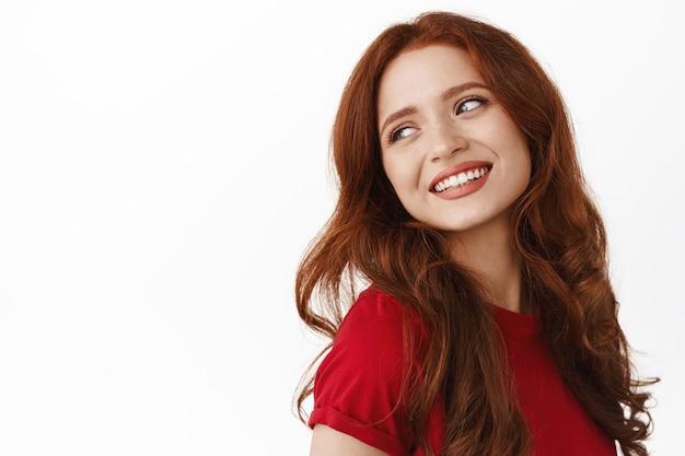 Kobieta, patrząca za ramię beztroska, uśmiechnięta i patrząca z zamyślonym romantycznym uśmiechem, stojąca w t-shircie na białym