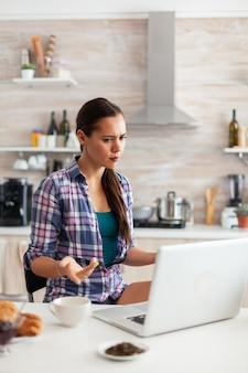 Kobieta patrząca zdezorientowana na ekran laptopa podczas pracy w domu w kuchni