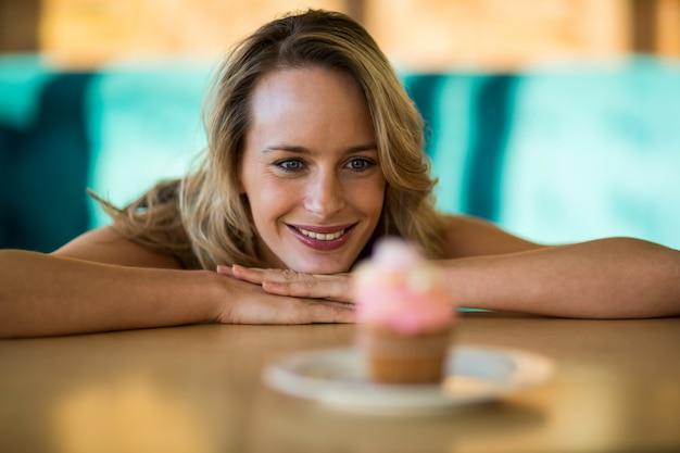Kobieta patrzeje babeczkę na talerzu