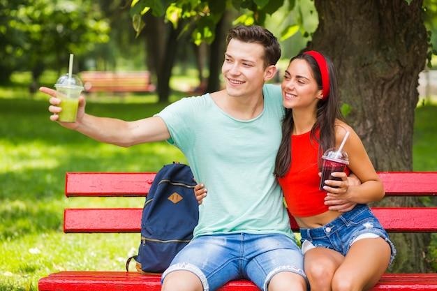 Kobieta patrzeje chłopaka wskazuje w kierunku coś trzyma zdrowych smoothies