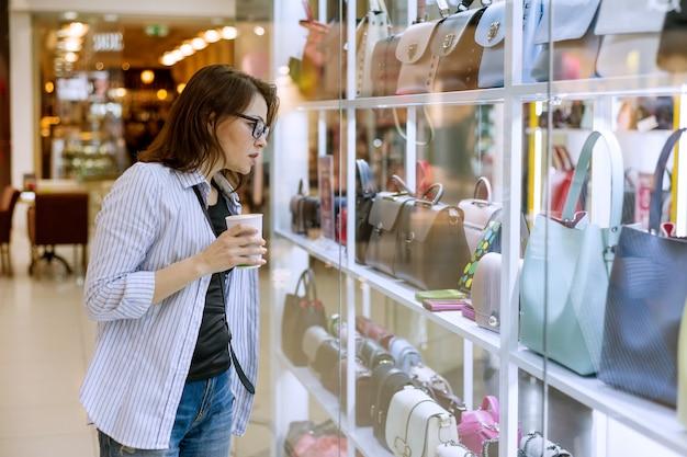 Kobieta patrzeje gablotę wystawową z torbami i akcesoriami
