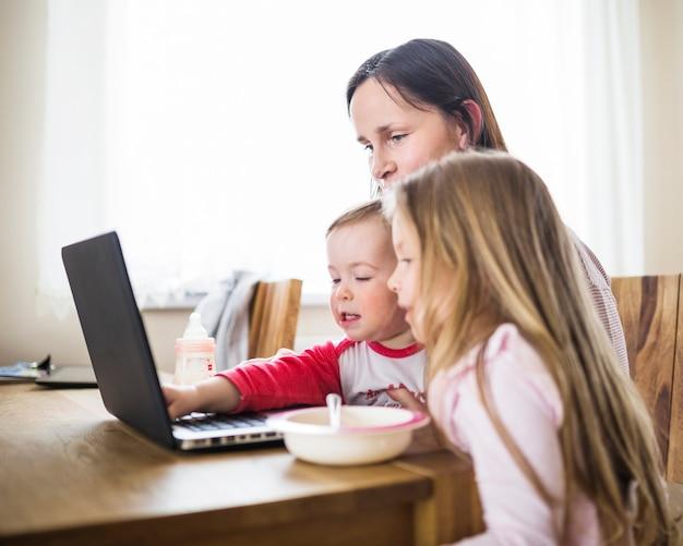 Kobieta patrzeje jej dzieci używa laptop