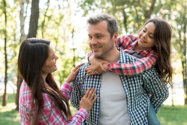 Kobieta patrzeje jej męża niesie ich córki przy parkiem