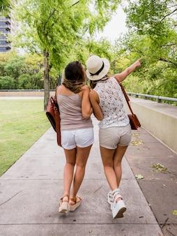 Kobieta patrzeje jej przyjaciela wskazuje przy coś w parku