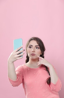 Kobieta patrzeje jej telefon i bierze selfie