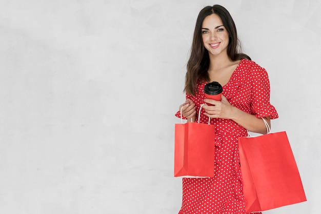 Kobieta patrzeje kamera z kawą i torba na zakupy