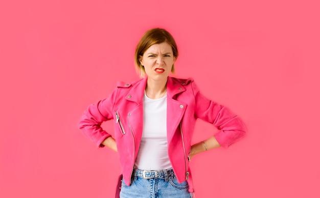 Kobieta patrzeje kamerę i czuje oburzony na różowym tle.