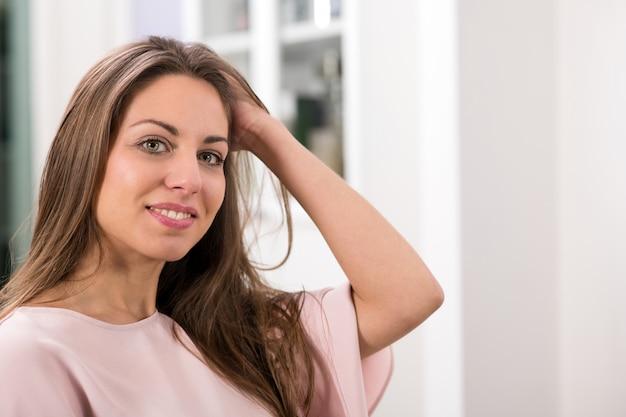 Kobieta patrzeje kamerę i wzruszającego włosy