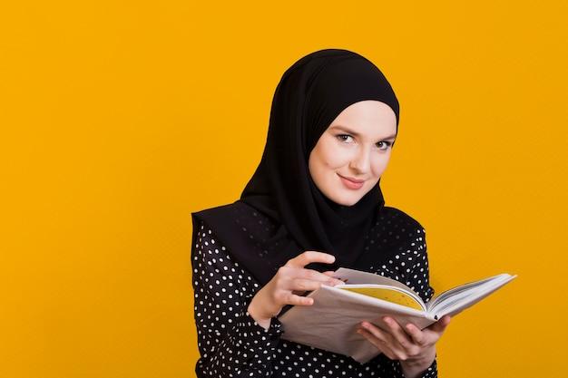 Kobieta patrzeje kamery mienia książkę w ręce nad powierzchnią