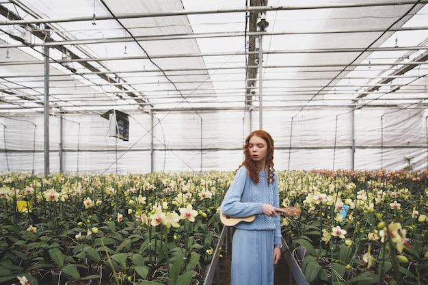 Kobieta patrzeje kwiaty w oranżerii