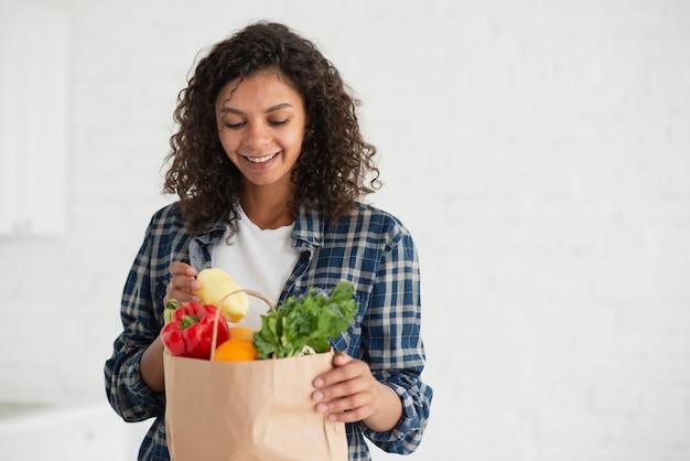 Kobieta patrzeje na warzywach z torby