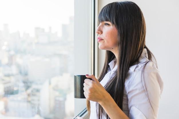 Kobieta patrzeje nadokiennego trzyma filiżankę kawy filiżanka