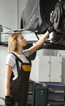 Kobieta patrzeje oponę samochód w auto usługa