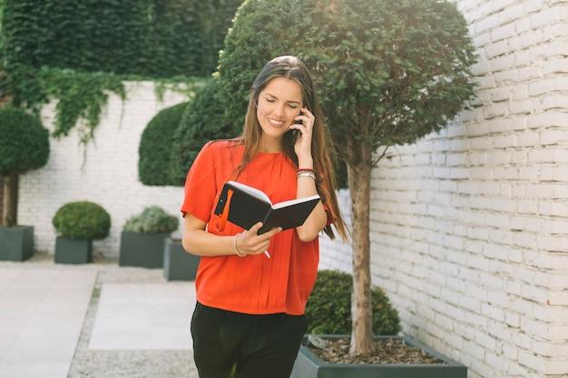 Kobieta patrzeje rozkład w dzienniczku podczas gdy opowiadający na telefonie komórkowym
